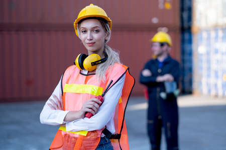 Foreman woman worker stand with confidence by arm-crossed and look at camera with his cargo container co-worker stand in background in workplace area. Stock Photo