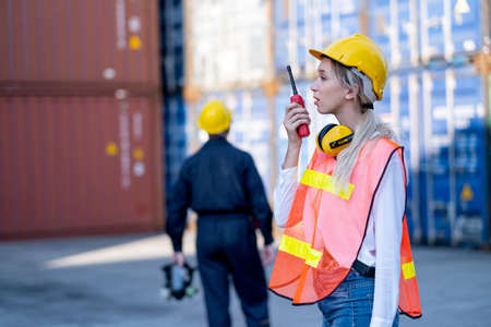 Foreman or cargo container woman worker use walkie talkie to communicate with her team and co-worker technician stand on background.
