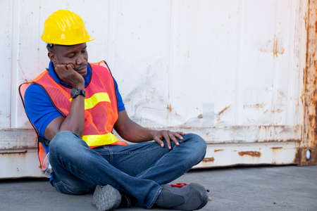 African American foreman or container worker sit and look like sleep to relax after finish his work in workplace.