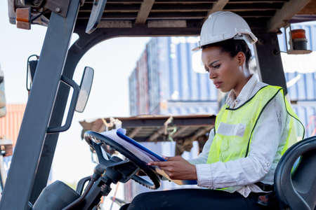 African American cargo container woman worker hold the document and look with serious emotion and sit in forklift truck during working in workplace.