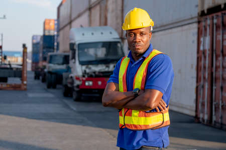 African American foreman or cargo container worker stand with confidence arm crossed in front of truck in workplace area and also look at camera.