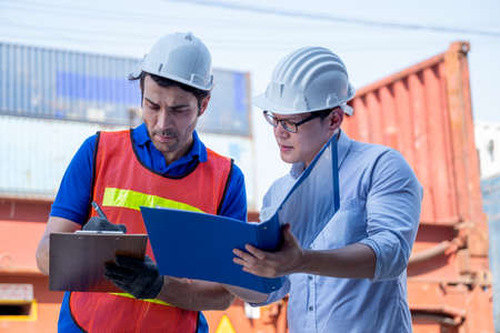 Foreman and cargo container worker discuss together with document in workplace area. Concept of good management system and teamwork in delivery business. Stock Photo