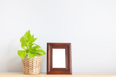 Golden pothos and photo frame on wood table Foto de archivo - 123524802