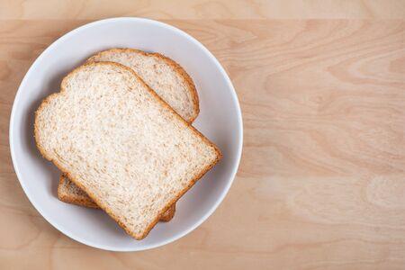 Top view of sliced wholegrain bread on wood Foto de archivo - 129560039