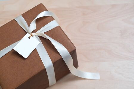Gift Box on wood talbe with blank card, copy space Foto de archivo - 129560087