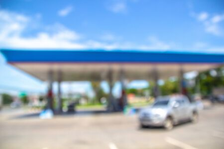 Car gas station is filling with oil. Blur image.