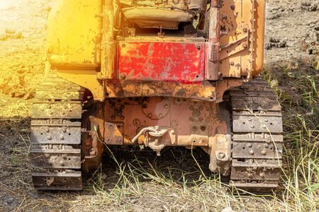 Old yellow-tone tracked tractors, heavy-duty