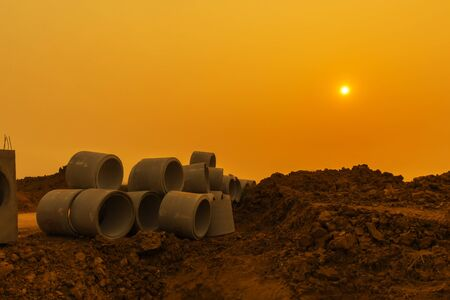 culvert: Concrete drainage pipe in construction site. Sunset background. Stock Photo