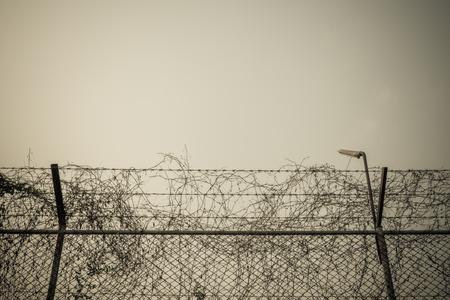 einrollen: Stacheldraht als Barrikade gegen Eindringling und Quarant�ne auf einem d�steren Himmel bew�lkt. Lizenzfreie Bilder