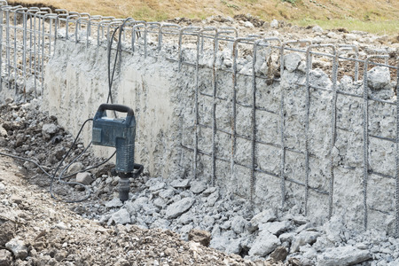 patching: Pneumatic hammer drill equipment breaking concrete at wall construction site Stock Photo