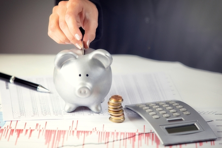 finance: Female hand putting coin in piggy bank, on the office desk  Stock Photo