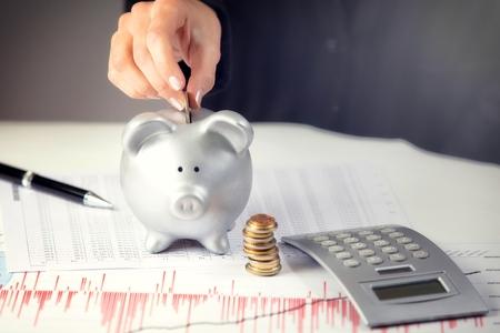 banco dinero: Mano femenina que pone la moneda en la hucha, en el escritorio de oficina
