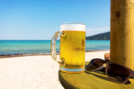 Pint of cold beer on top of the beach table  photo