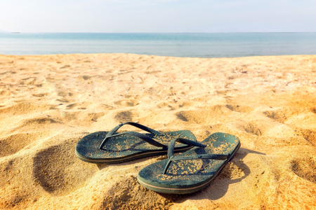 foot ware: A pair of flipflops,on the beach