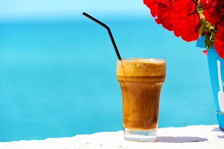cappuccino foam: Ice coffee against sea background  Stock Photo