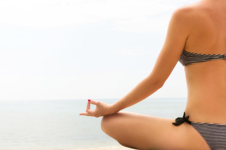 Close up of a female seated in lotus position,meditating at the sea  photo