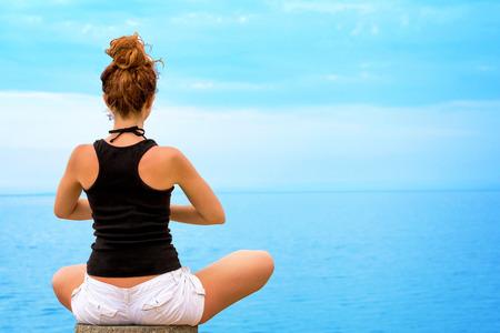 Joven mujer haciendo yoga, mirando el horizonte del océano
