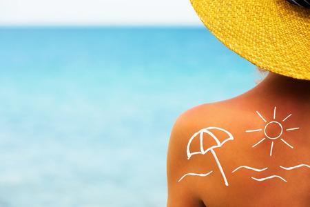 Suncream on back of woman shoulder
