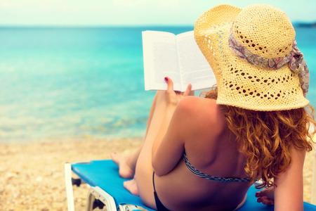 Krullend haar vrouwelijke lezen van een boek op het strand Stockfoto