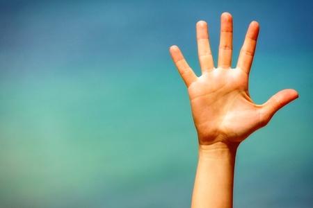 manos abiertas: Primer plano de una mano abierta, sobre fondo azul