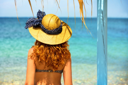 Curly haired woman looking at the sea  photo