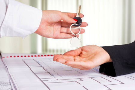 Architect hand presenting house key to a client  photo