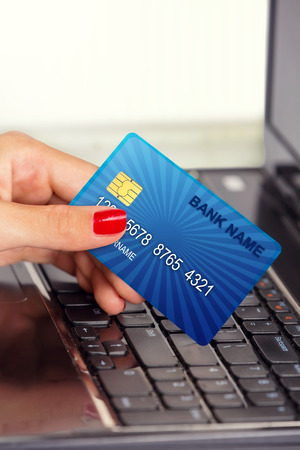 mastercard: Close up of a female hand holding credit card, in front of laptop keyboard