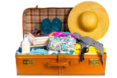 open suitcase: Packed vintage suitcase full of vacation items. Stock Photo