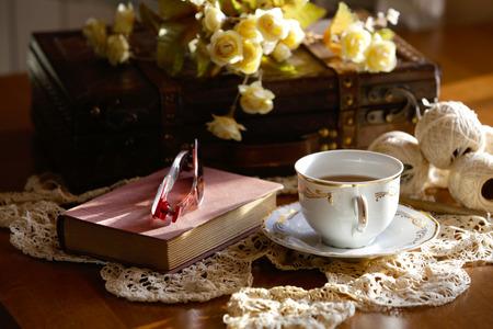 紅茶のカップ、閉じた本とかぎ針編みのレースの眼鏡のロマンチックな組成物。 写真素材
