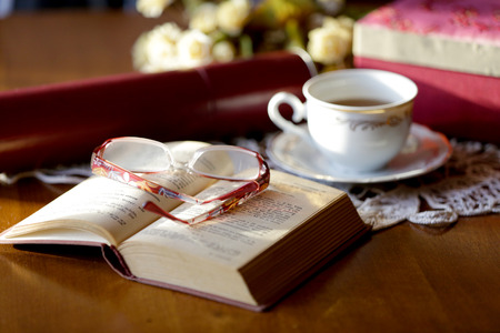 Cup of tea, book and glasses on old wooden table. Zdjęcie Seryjne