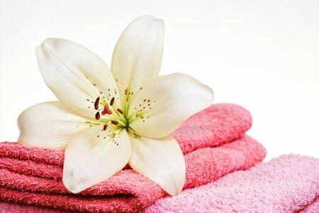 Rosa Handtuch und weiße Lilie Blume, isoliert auf weißem Hintergrund.