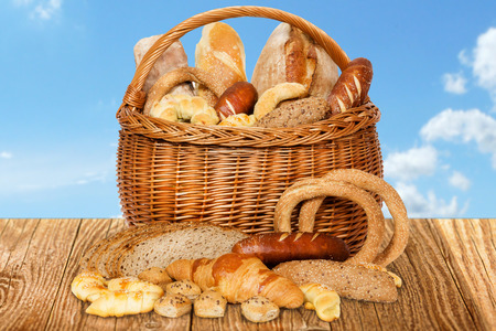 Composition with bakery products in wicker basket, on wooden table, outdoor.
