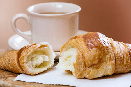 light breakfast: Fresh croissant and cup of tea, on kitchen table. Stock Photo
