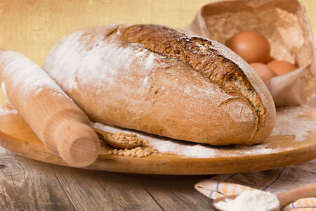 traditional goods: Homemade bread and ingredients, on a rural vintage wooden table. Stock Photo