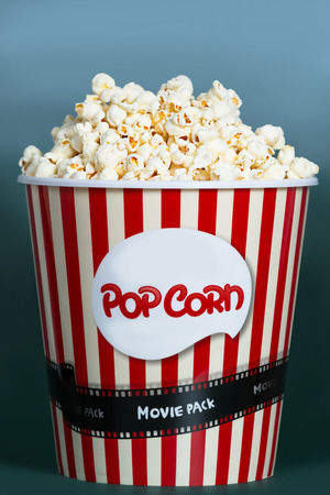 pop corn: Popcorn in red and white cardboard box for cinema, isolated on blue background.
