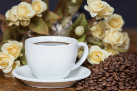 Beautifully arranged cup of coffee among coffee beans and flowers. photo