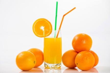 Glass of orange juice and oranges, isolated on white background. photo
