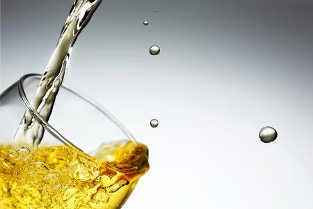 Splashing beverage poured inside a glass.