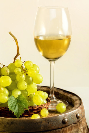 Glass of white wine and green grapes on old barrel, in light cellar. photo