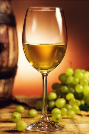 Glass of white wine in front of green grapes and old barrel, placed on wooden table. photo