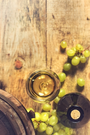 Glass of wine,bottle, green grapes and old barrel. photo