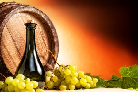 Bottle of wine in front of wine barrel with white grapes. photo