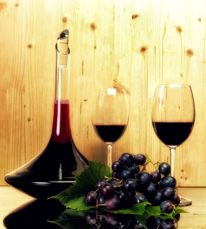 Luxury wine collection- two glasses, bottle, and dark blue grapes. Light wooden background and reflection table. photo