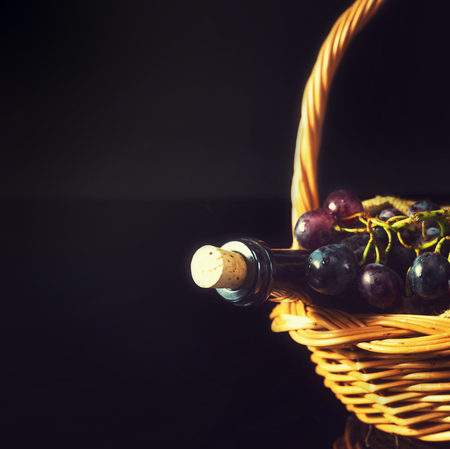 Close up of a closed wine bottle and blue-black grapes in wooden basket, against black . photo