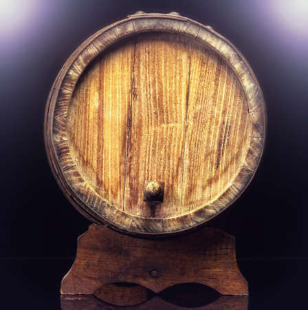 Old wooden barrel isolated on dark . photo