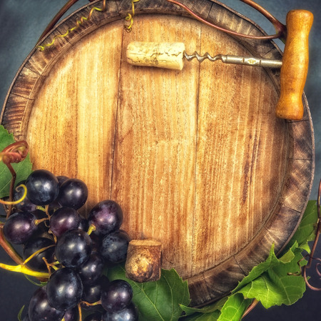 Top view of the old wooden barrel, with dark blue grapes and bottle opener on it. photo