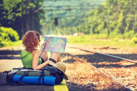 viaggi: Ragazza che porta zaino azienda map, in attesa di un treno.