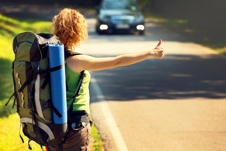 hitch: Girl wearing backpack holding map, hitch hiking. Stock Photo