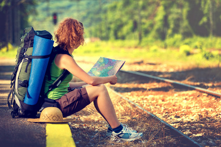 going nowhere: Girl wearing backpack and holding map, waiting for a train. Stock Photo