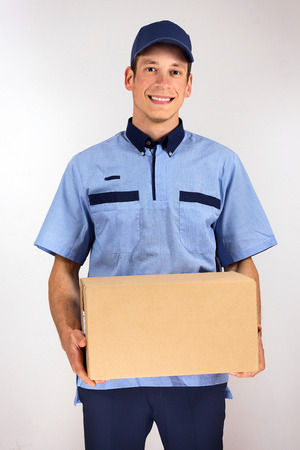 man carrying box: Handsome young delivery man carrying carton box.